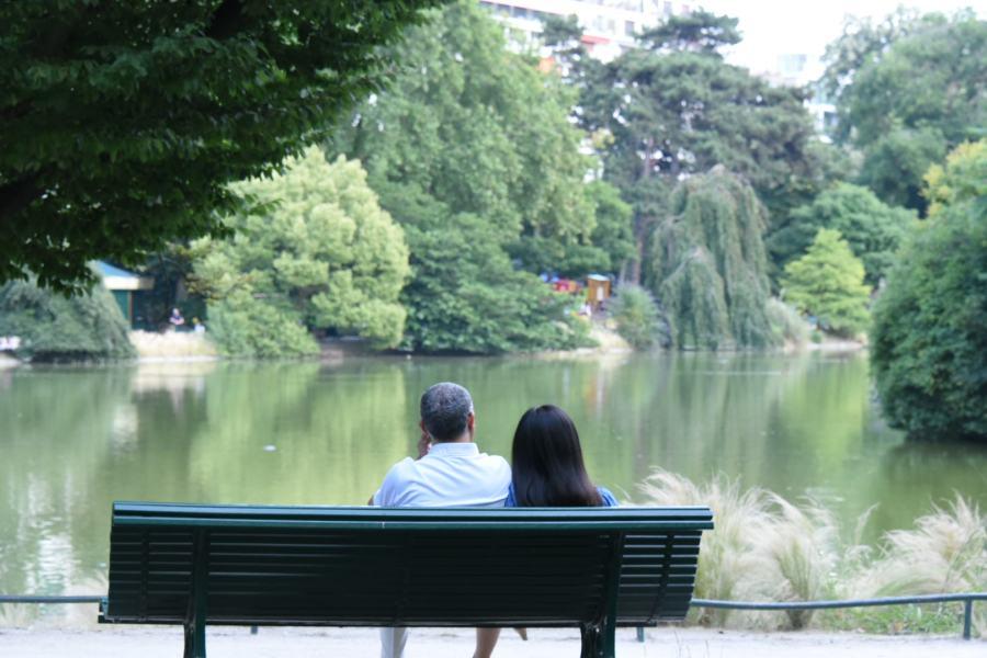Un couple assis sur un banc face à un lac