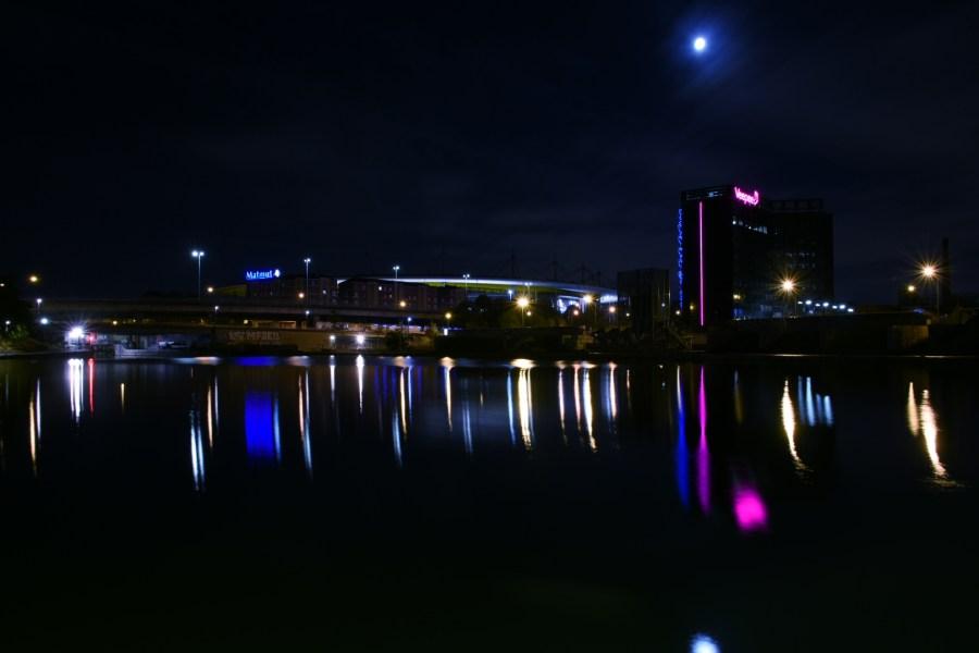 Le canal reflète les lumières de Saint-Denis, avec le stade de France au fond