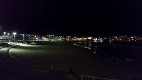 A blurry nighttime photo of Bondi beach