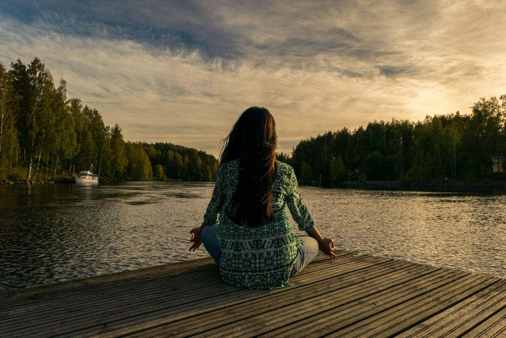 woman on dock meditating at sunset