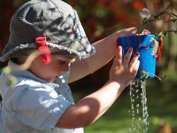 植木鉢から水を抜く子供