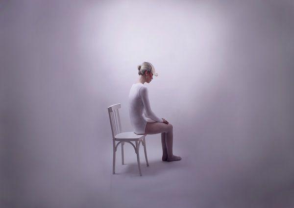 一人ぼっちで白い部屋に座る人