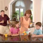 キッチンでオレンジジュースを注ぐ