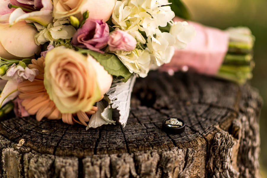 Wedding rings sit beside the bride's bouquet.