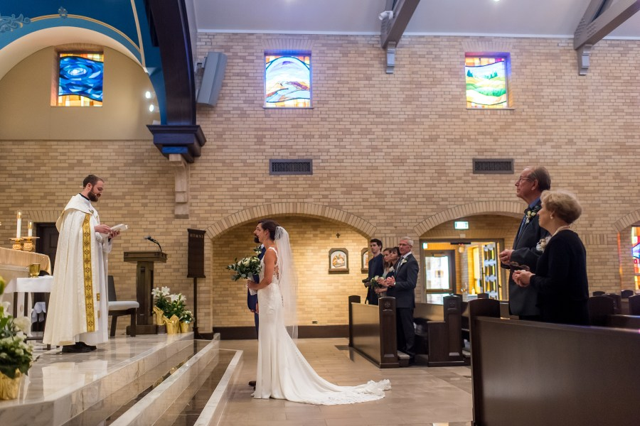 Standing at the alter for a wedding Mass at Our Lady of Lourdes Catholic Church in Denver, Colorado.