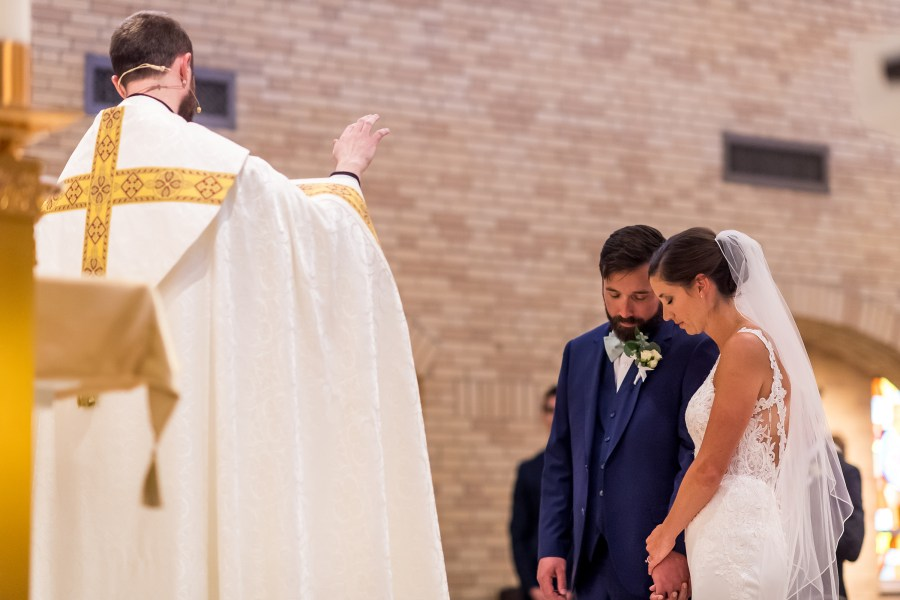 Receiving a blessing during a wedding at Our Lady of Lourdes Catholic Church in Denver, Colorado