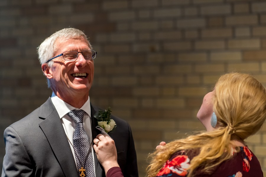 Boutonniere pinned on father of the bride at Our Lady of Lourdes Catholic Church in Denver, Colorado