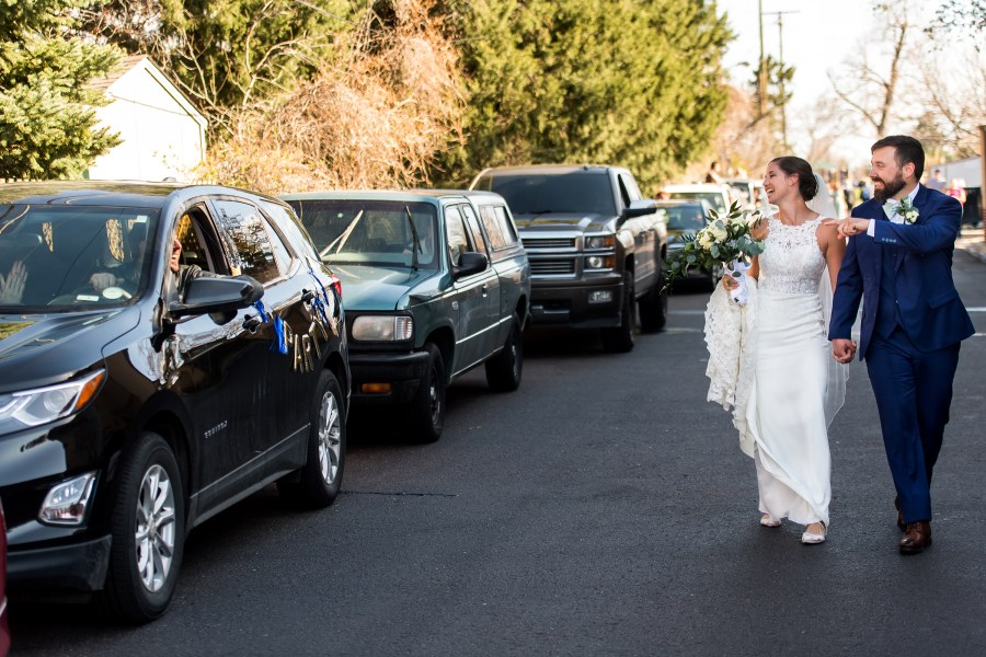 Friends line up in their cars to congratulate bride and groom after their wedding at Our Lady of Lourdes Catholic Church in Denver, Colorado.