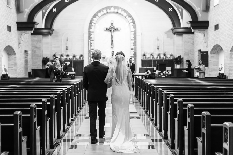 The bride walks in with her father to an empty church at Our Lady of Lourdes Catholic Church in Denver, Colorado.