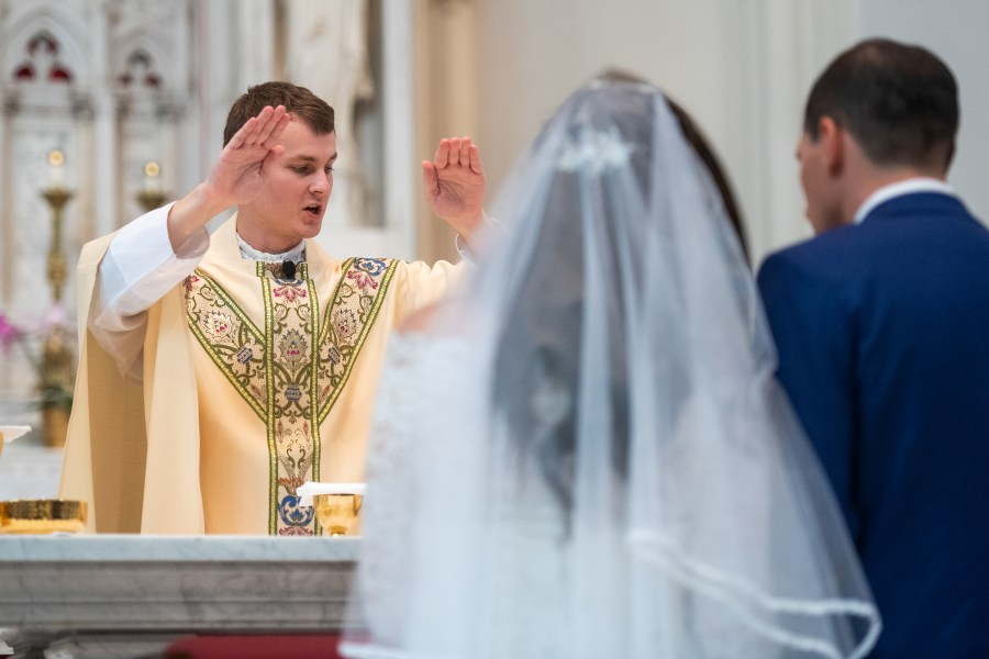 A priest prays over the bride and groom during their wedding at the Cathedral Basilica of the Immaculate Conception in Denver, Colorado.
