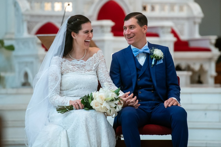 Bride and groom laugh during their wedding at the Cathedral Basilica of the Immaculate Conception in Denver, Colorado.