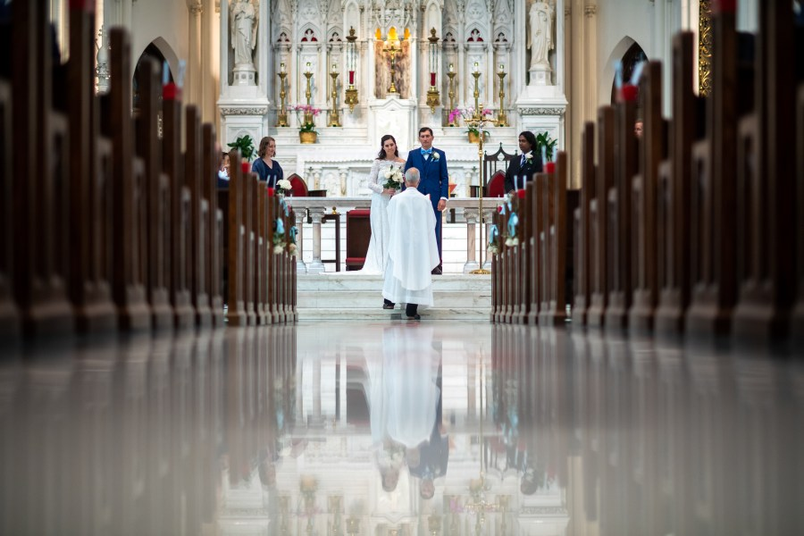 Bride and groom during their wedding at the Cathedral Basilica of the Immaculate Conception in Denver, Colorado.