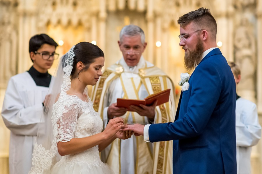 Bride puts on the ring of the groom at Our Lady of Mt. Carmel in Littleton, Colorado.