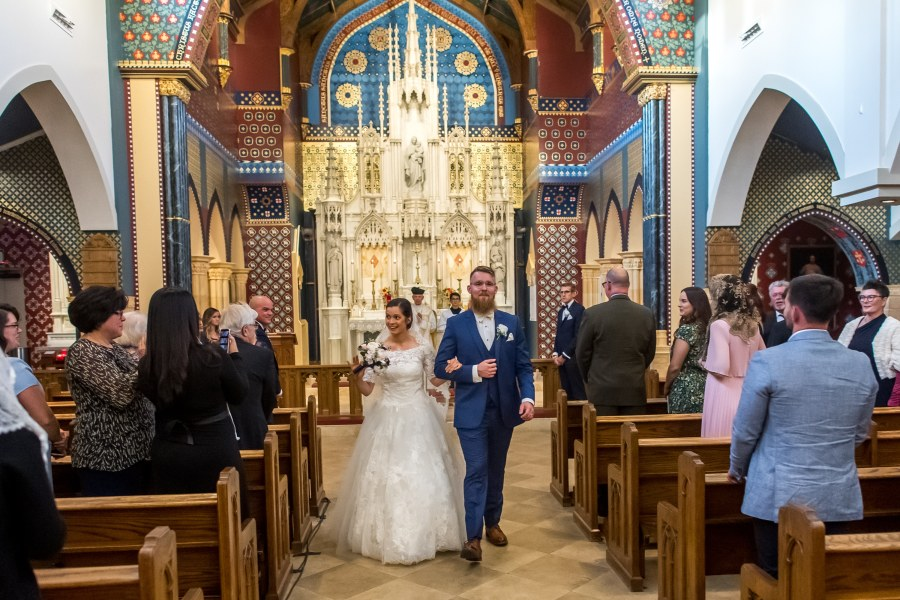 Bride and groom walk down the aisle after a wedding at Our Lady of Mt. Carmel in Littleton, Colorado.