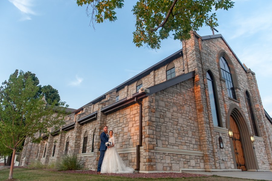 Bride and groom pose outside the church after a wedding at Our Lady of Mt. Carmel in Littleton, Colorado.