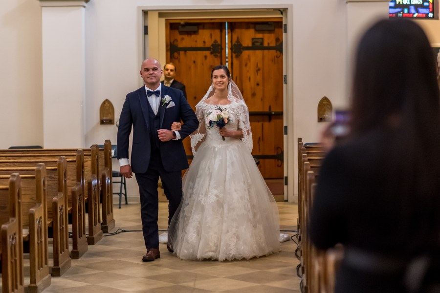 Bride walks down the aisle of her wedding at Our Lady of Mt. Carmel in Littleton, Colorado.