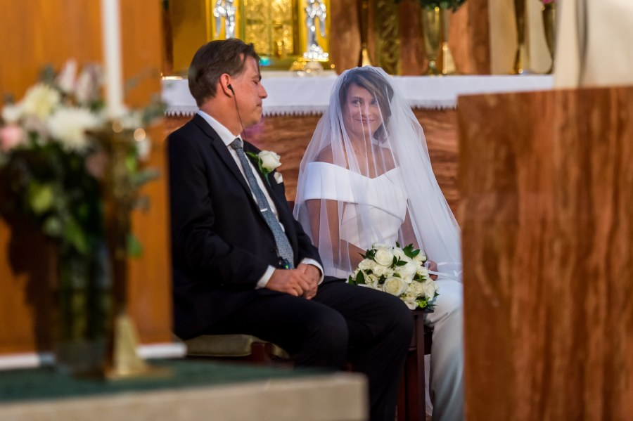 The bride and groom smile at one another during a wedding Mass at St. Joseph Catholic Church in Fort Collins, Colorado, on August 8, 2020.