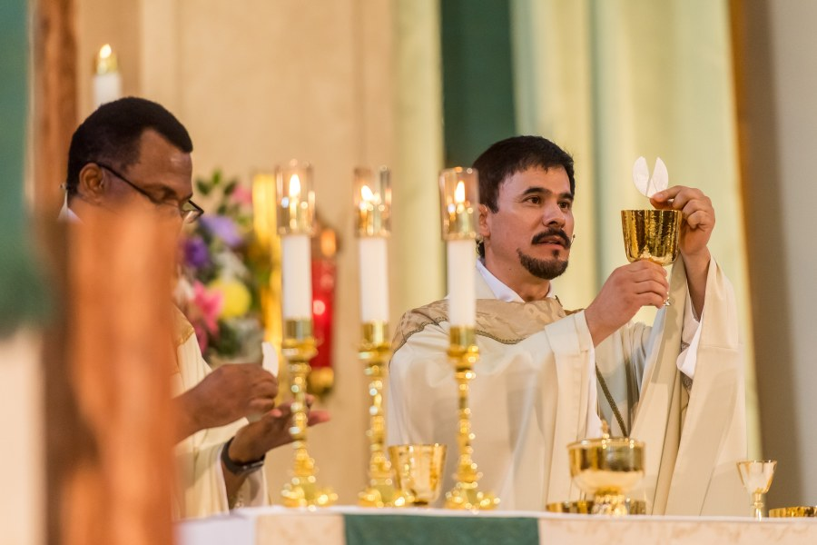 The priest holds the consecrated host up during a St. Joseph Catholic Church wedding on August 8, 2020, in Fort Collins, Colorado.