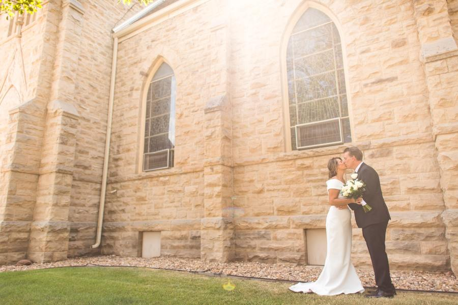 Bride and groom kiss for their St. Joseph Fort Collins Catholic Church wedding photos on Aug. 8, 2020, in Colorado.