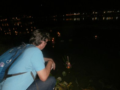 Rand pushing his kratong into the river
