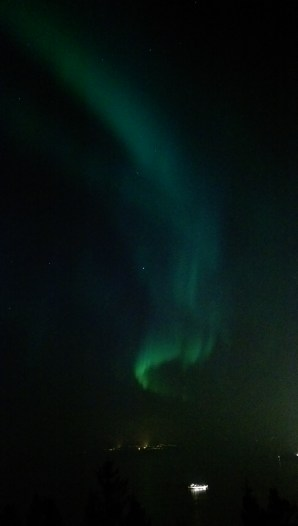 A huge curtain of lights running above the coastline of Trondheim
