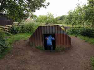 Small boy in blue coat climbing into a traditional Anderson Shelter