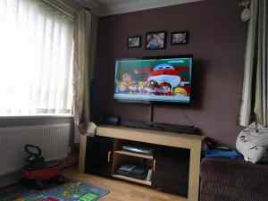 Picture of a wall mounted tv playing Super Wings cartoon