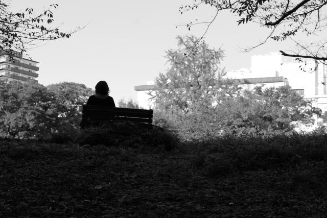 公園で一人ベンチに座っている後姿