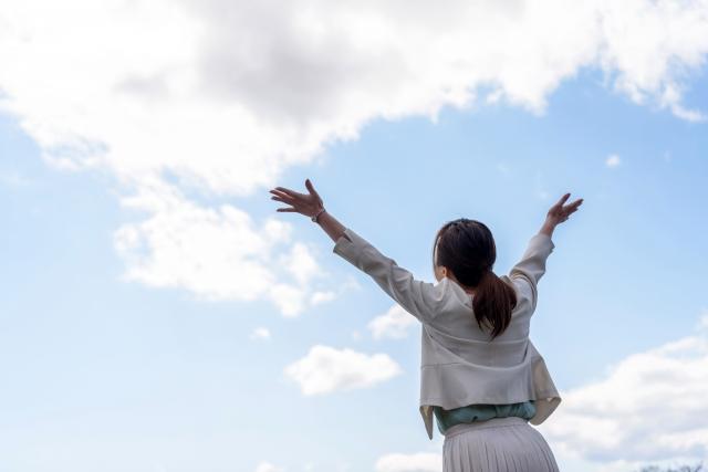 両手をあげて青空を仰ぎ見る女