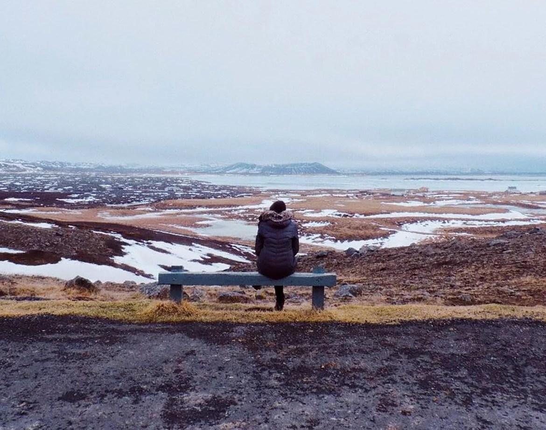 Sentada em um banco, admirando a paisagem