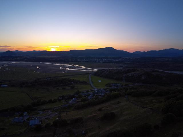 Stargazing UK - Where To See The Best Night Skies -Fontburn Reservoir in Northumberland is a popular place for fishing and walking, seen her under the stars at night -Aerial view, Drone panorama colorful sunset over hills, sea, Snowdonia mountains in background in North Wales