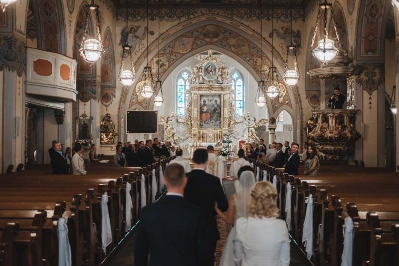 Przebieg ślubu kościelnego w Borach Tucholskich - wejście Pary Młodej wraz z księdzem