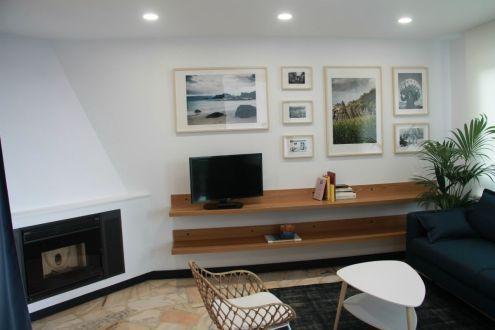 Salón con chimenea y cuadros del Apartamento Lapamán