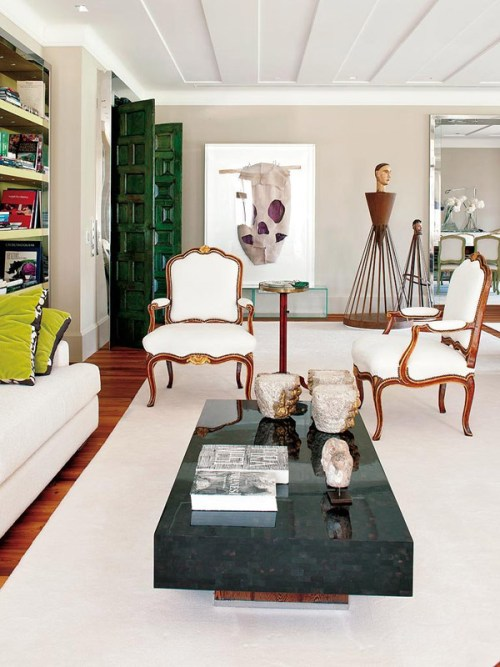 contemporary-glam-in-Portugal-living-room-green-doors-skull-art-French-bergere-chairs-black-horn-table