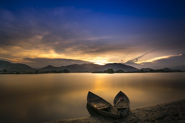 2 wooden boats in foreground with lake, mountains and sunrise in background