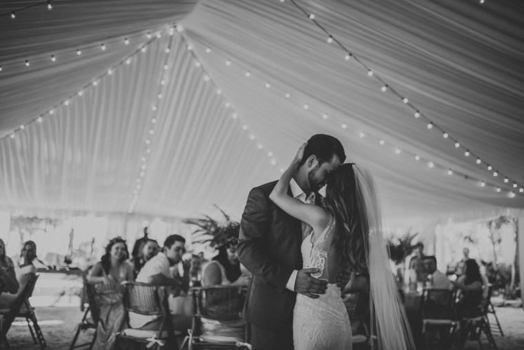 Bride and groom slow dance under tent with festival lights.