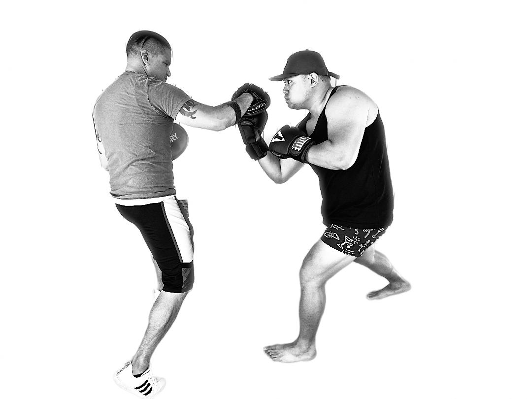 Two men training boxing mitts.