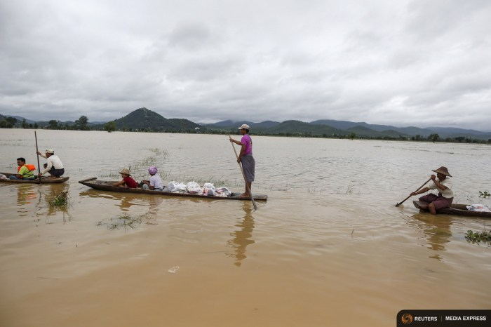 Residents transport aid on boats for their flooded village at Kawlin township, Sagaing division, Myanmar July 23, 2015. REUTERS/Soe Zeya Tun/Files