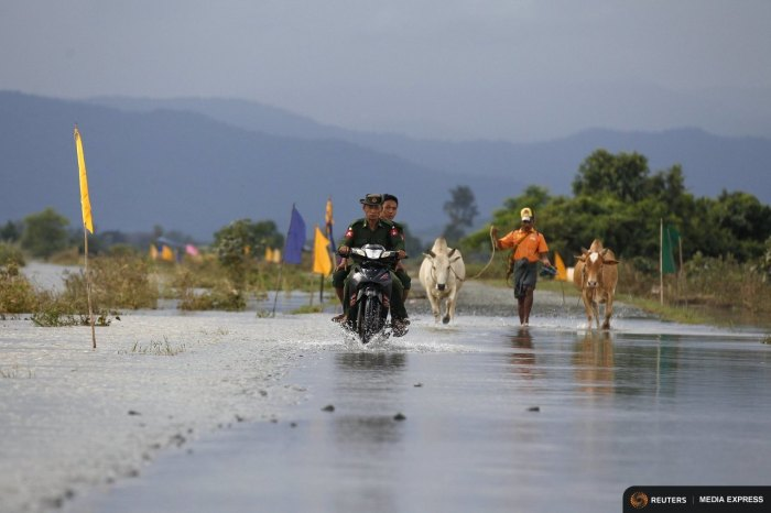 Soldiers ride a motorbike on a flooded road at Kawlin township, Sagaing division, Myanmar July 23, 2015. REUTERS/Soe Zeya Tun /Files
