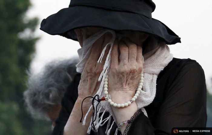 A woman reacts after praying for victims in front of the cenotaph for victims of the 1945 atomic bombing, at Peace Memorial Park in Hiroshima, western Japan, August 6, 2015, on the 70th anniversary of the world's first atomic bombing.   REUTERS/Toru Hanai