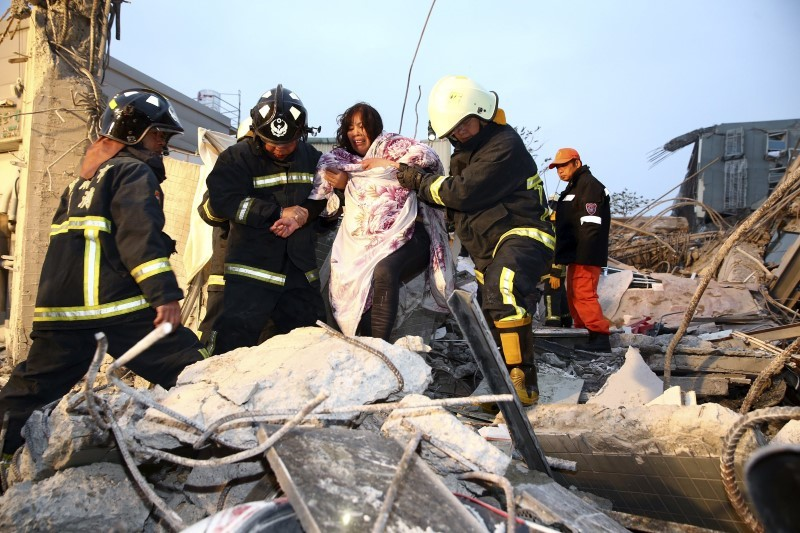 Rescue personnel help a victim at a damaged building after an earthquake in Tainan, southern Taiwan, February 6, 2016. REUTERS/Stringer