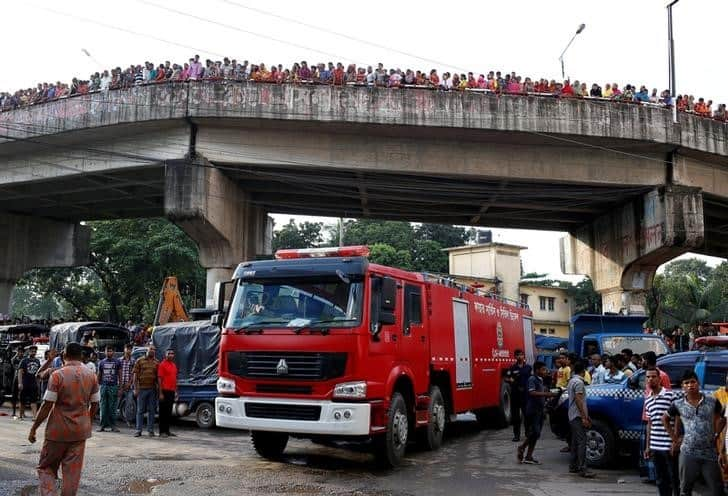 People stand on a bridge as a firefighter truck drives at the site of a fire at a packaging factory outside Dhaka, Bangladesh, September 10, 2016. REUTERS/Mohammad Ponir Hossain