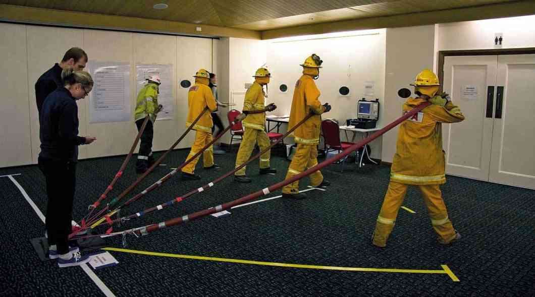 Volunteer firefighters performing physical tasks during a simulated bushfire deployment.