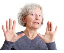 Geschockte Seniorin hält ihre Hände in ablehnender Haltung vor sich