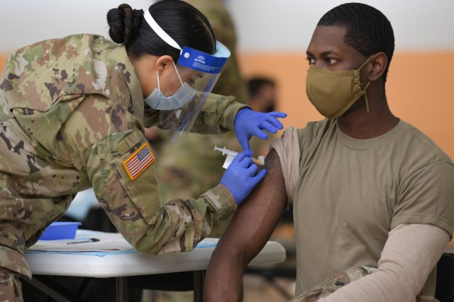 """U.S. Army Spc. Eyza Carrasco, left, with 2nd Cavalry Regiment, administers a COVID-19 vaccination at the 7th Army Training Command's (7ATC) Rose Barracks, Vilseck, Germany, May 3, 2021. The U.S. Army Health Clinics at Grafenwoehr and Vilseck conducted a """"One Community"""" COVID-19 vaccine drive May 3-7 to provide thousands of appointments to the 7ATC community of Soldiers, spouses, Department of the Army civilians, veterans and local nationals employed by the U.S. Army."""