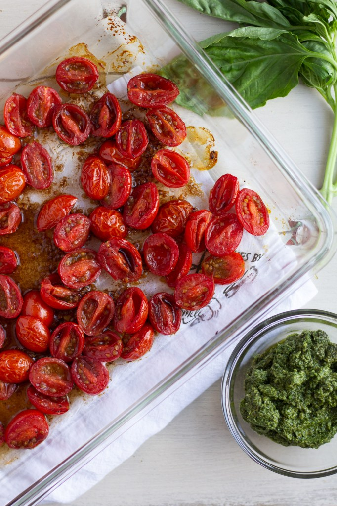 Pan of balsamic roasted cherry tomatoes with a bowl of homemade walnut pesto and fresh basil