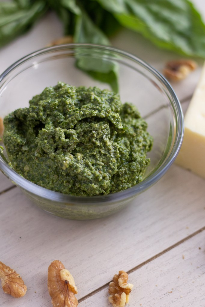 Bowl of homemade walnut pesto with fresh basil in the background