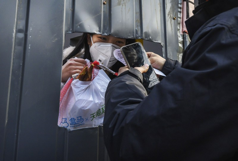 A Chinese woman wears a protective mask as she accepts a package from a courier through a cutout hole on Feb. 25, 2020 in Beijing, China.