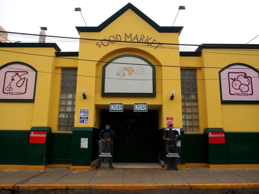 Municipal police guard the doors of a food market closed for sanitary measures, due to Covid-19, in a neighborhood of the Lima on May 27.
