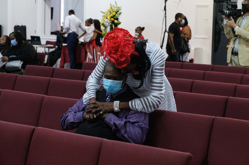 Donna Mays hugs Jamel Floyd's cousin, Mark Lumpkin, during the funeral on June 30.